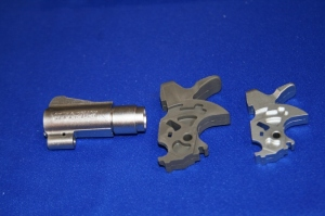 The as-cast metal powder-wax-polymer product is in the center with the finished revolver hammer on the right.
